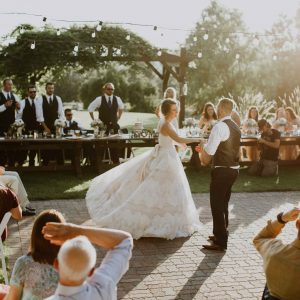 Bride and groom dancing at golden hour under bistro lights at a July wedding at Beacon Hill Event Venue, in Spokane, WA